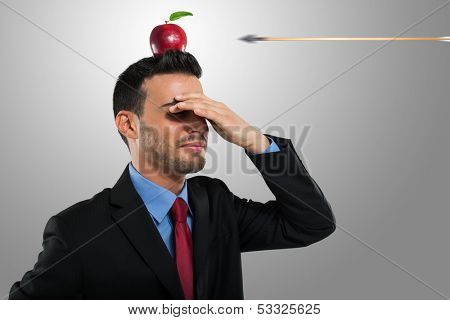 Risk management concept, arrow hitting an apple on a businessman's head