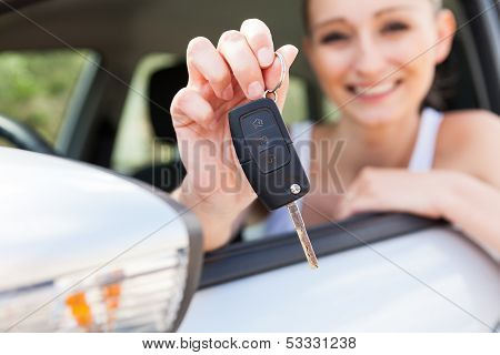 Young Smiling Woman Sitting In Car Taking Key