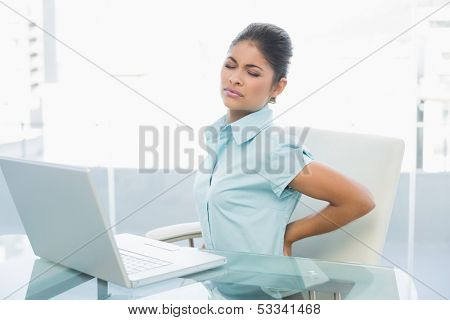 Young businesswoman suffering from back ache in front of laptop in the office