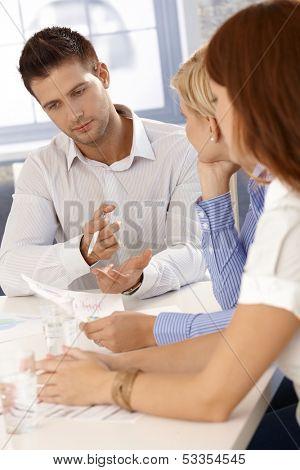 Brainstorming at businessmeeting, businessman concentrating on task.