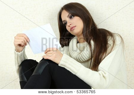 Lonely sad woman near wall