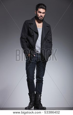 full body picture of a fashion man with beard standing with hands in pockets and looking away from the camera