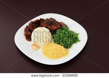 Brazilian Feijoada on a plate on brown leather background.