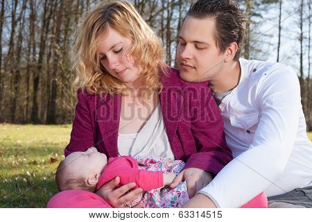 Young Parents Caring Of Their Little Baby Girl