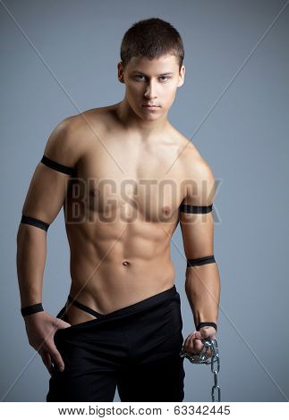 athletic man dance striptease with chain
