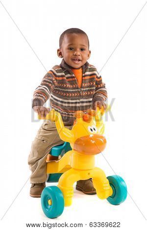 One Year Old Boy Riding toy tricycles isolated on White Background