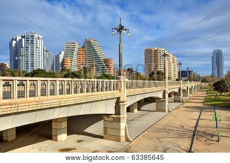 Bridge across old river bed of Turia and contemporary residential buildings on background in Valencia, Spain.