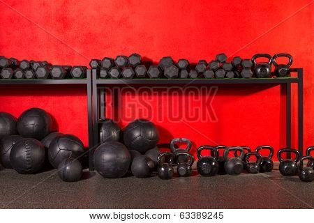 Kettlebell dumbbell and weighted slam balls weight training equipment at gym red walls poster