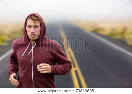 Athlete man running training on road in fall in sweatshirt hoodie in autumn. Male runner training outdoors jogging in nature.
