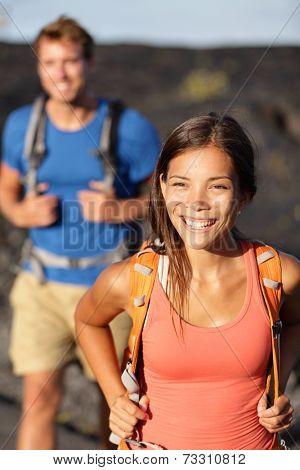 Hiking couple - Asian woman hiker walking on lava field on Hawaii. Tourists hikers on hike near Kilauea volcano around Hawaii volcanoes national park, USA.