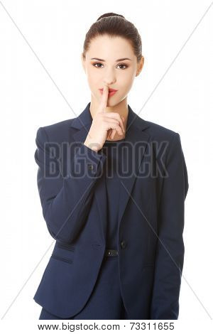 Hush. Businesswoman with finger on her lips gesturing for quiet poster