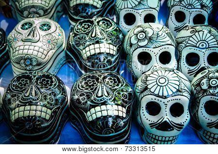 Traditional mexican day of the dead souvenir ceramic skulls at market stall poster