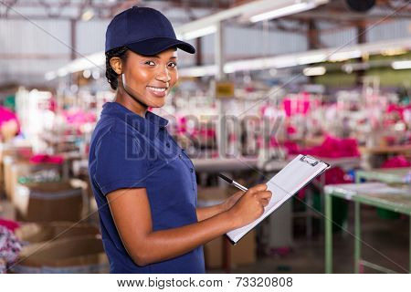 young female african textile factory worker in production area