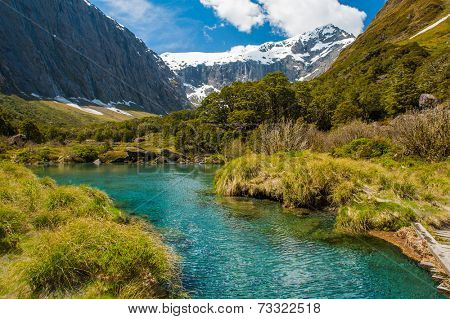 Gertrude Saddle with a snowy mountains and a turquoise lake, Fiordland national park, New Zealand South island poster