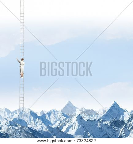 Businesswoman standing on ladder high above mountains