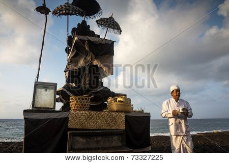 BALI, INDONESIA - SEPTEMBER 19, 2014: A priest performs the prayers for families at the Nyaben ceremony, a day to throw the cremated ashes into the sea, a sign of releasing the soul for reincarnation.