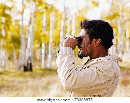 African man looking through binoculars