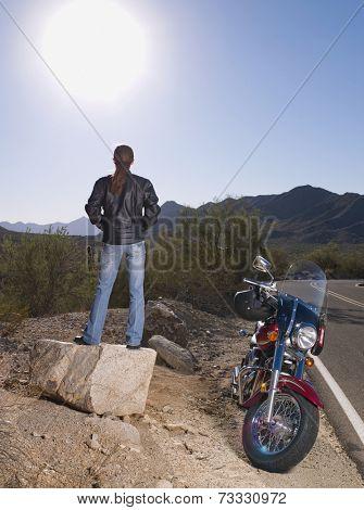 Hispanic woman standing next to motorcycle