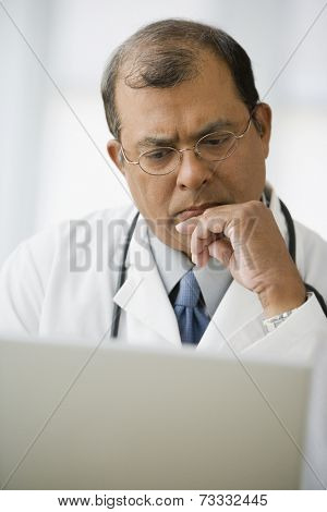 Indian male doctor looking at laptop