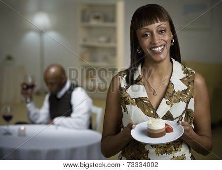 African woman holding plate of dessert