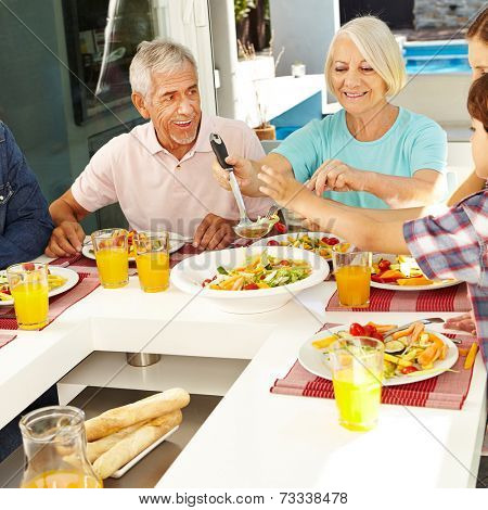 Happy vegetarian senior couple eating lunch with family