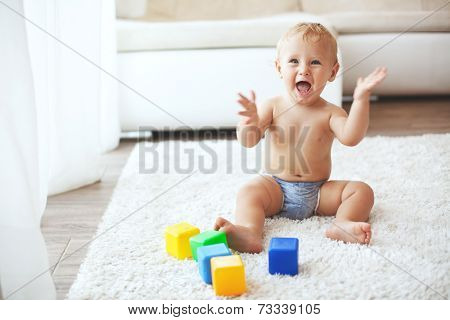 Toddler playing with toys on a white carpet at home