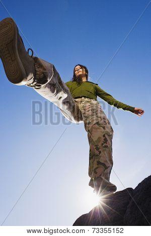Hispanic woman stepping off rock
