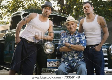Hispanic father and adult sons in front of car