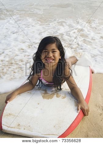 Pacific Islander girl laying on boogie board