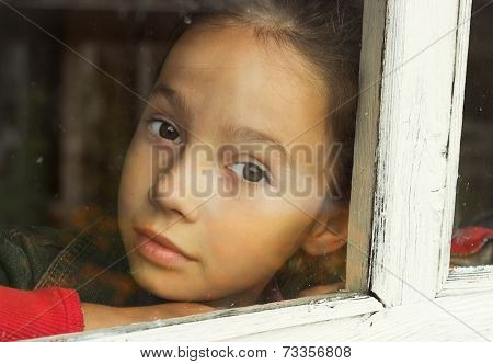 sad little girl looking through an old window