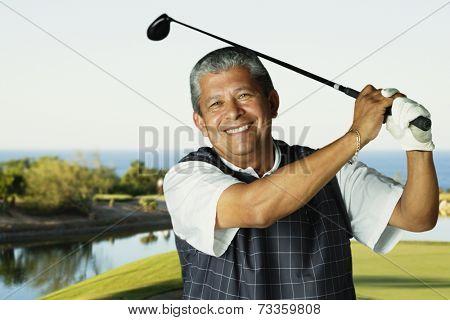Hispanic man swinging golf club