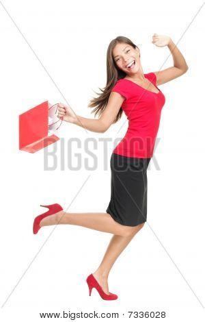 Mujer en alegría corriendo sosteniendo el bolso de compras