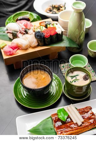 Premium Quality Grilled Eel, Miso Soup, Sake And Sushi Rolls Served In Japanese Restaurant. Asian Fo
