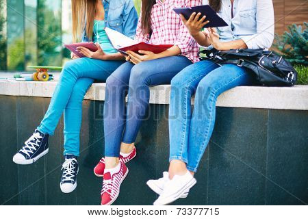 Slim legs of three females in tight jeans