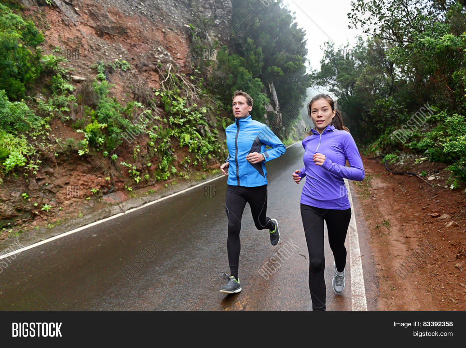 b7cf03214b19f Healthy lifestyle people running on country road exercising. Runners  jogging on mountain road training for