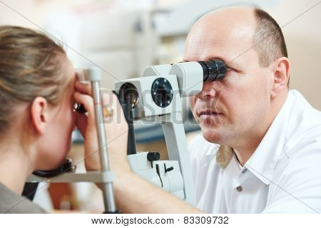 Optometry concept. Male optometrist optician doctor examines eyesight of female patient in eye ophthalmological clinic