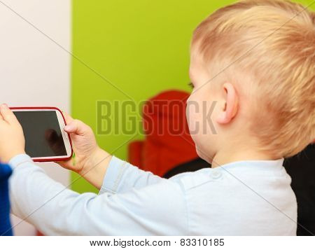 Little Boy Child Playing Games On Mobile Phone.