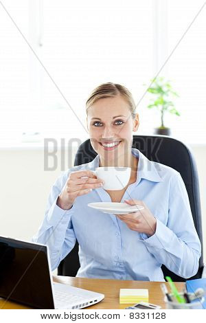 Cheerful Young Businesswoman Drinking Coffee Smiling At The Camera