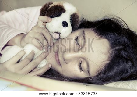 Little sweet girl sleeping and hugging her toy