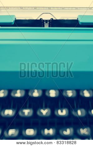 closeup of a retro blue typewriter with a blank page in its roller, with a filter effect