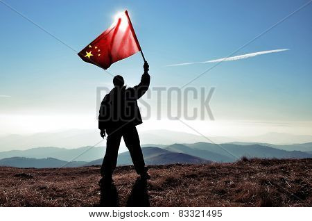 Successful man waving Chinese flag on a mountain peak