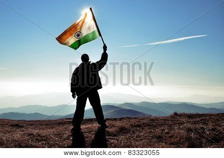 Man holding high Mexico flag on a peak