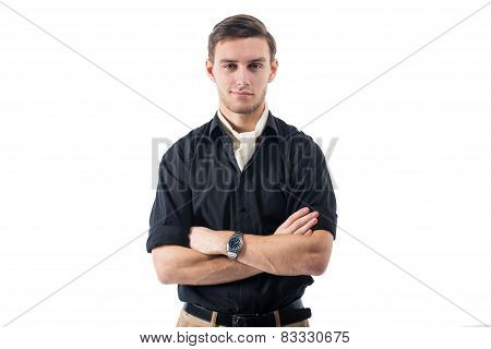 Young strong businessman  in black shirt with white cravat stands against the wall hands crossed.