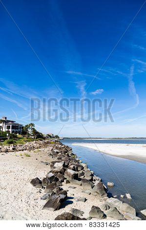 Rock Seawall Toward Homes Under Brilliant Sky