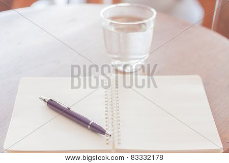 Pen And Blank Spiral Notebook On Wooden Table