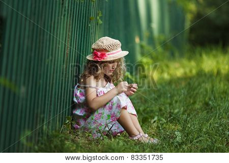 Girl Sits Leaning Against A Fence