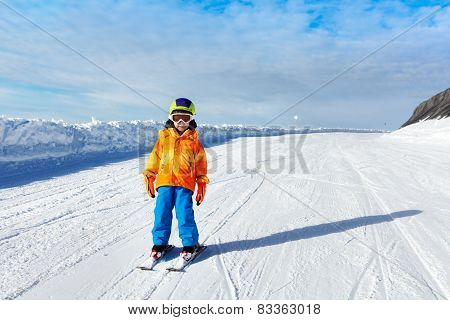 Small boy wearing ski mask stands on ski-track