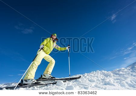 Young woman in mask holding ski poles and skiing