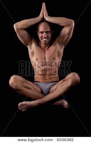 Young sexy muscle man on black background, sitting, lotus, posing poster
