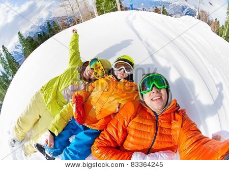 Happy family laying in snow and making selfie